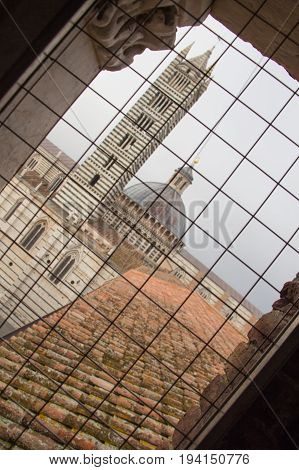 Italy Siena - December 26 2016: the view from iron grid window of Duomo di Siena or Metropolitan Cathedral of Santa Maria Assunta on December 26 2016 in Siena Tuscany Italy.