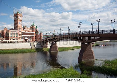 Yoshkar-Ola Russia - June 14 2017:A photo of a sunny day in Yoshkar-Ola with a view of the Sundays the bridge over the Kokshaga River and an administrative building on the other side of the river