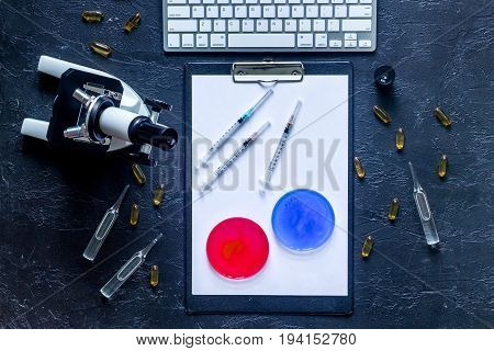 Workplace in laboratory. Microscope, ampoule, Petri dish, pad and pills on grey stone background top view.