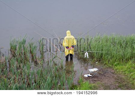 Yoshkar-Ola Russia - June 14 2017 A photograph of a fisherman in a raincoat fishing in the rain which stands in knee-deep in the river Kokshaga