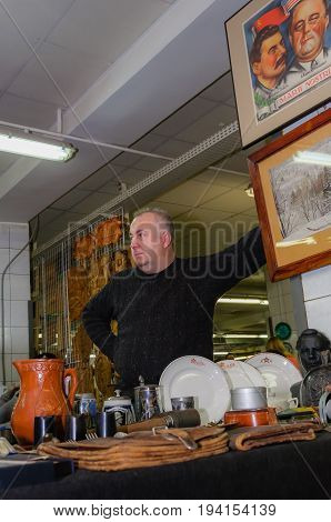 Moscow, Russia - March 19, 2017: Antique dealer, seller of political, rare military and communist symbols of the age of the USSR and World War II in the special antique market is waiting for interested buyers and collectors