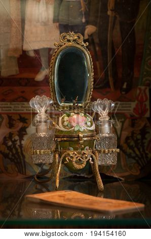 Moscow, Russia - March 19, 2017: A rare ancient female perfume set in the form of an Easter egg with a mirror and bottles of cologne is in the window of an antique store. A finely decorated thing, an elegant painting.