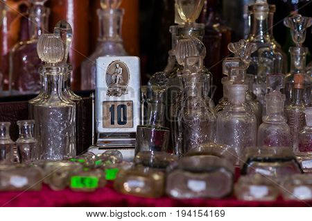 Moscow, Russia - March 19, 2017: Old mechanical perpetual calendar stands on the antiques store counter among vintage glass perfume and chemist's bottles, shows the date number 10