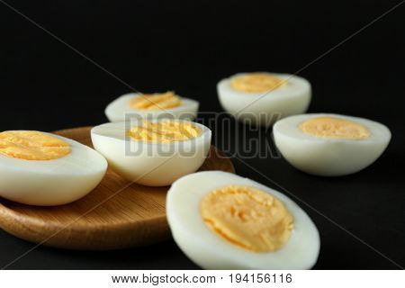 Wooden tray and hard boiled eggs on black background. Nutrition concept