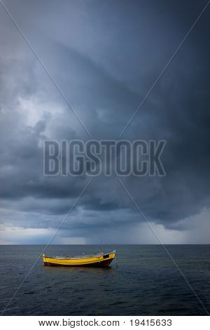 Yellow fishing boat on a sea against dramatic sky