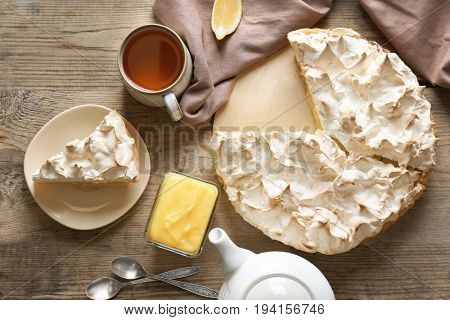 Yummy lemon meringue pie with tea on wooden table