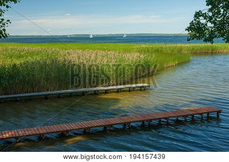 Sniardwy Lake with boardwalks in foreground and some yachts in background, Mazurien Region, Poland, Europe