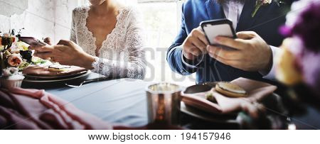 Newlywed couple using mobile phone