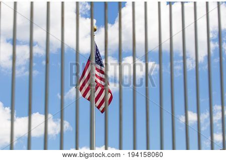 The USA flag waving over blue sky visible through fence grates.