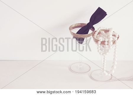 Elegantly simple gold rimmed martini glasses filled with a black bow tie and a string of pearls. White copy space.