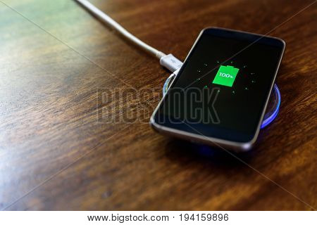 Smartphone charging on a charging pad. Wireless charging.