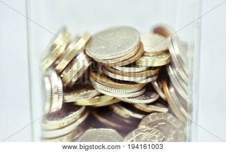 Close up of coins saved in a money jar