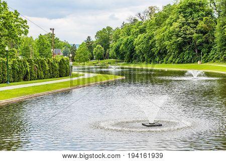 Harrisburg USA - May 24 2017: Italian Lake Park in Pennsylvania capital city with fountain and path