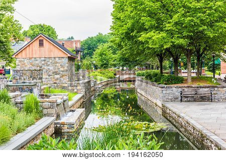 Frederick USA - May 24 2017: Carroll Creek in Maryland city park with canal and bench