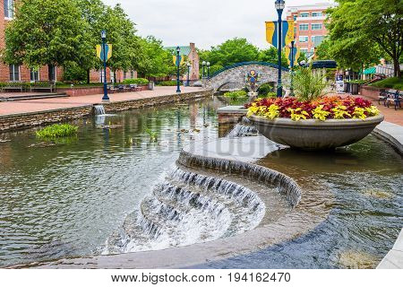 Frederick USA - May 24 2017: Carroll Creek in Maryland city park with canal bridge and fountain waterfall and flowers in summer