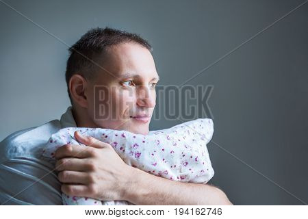 Closeup side profile portrait of young man holding a pillow looking and thinking