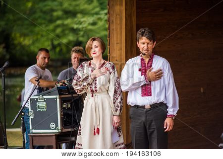 Silver Spring USA - September 17 2016: Two speakers with hand on heart for national anthem at 14th Washington Ukrainian festival near Washington DC at St. Andrew Ukrainian orthodox cathedral