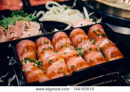 raw pork chop meat sliced on black plate.