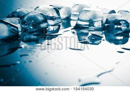 Melting ice on a table with reflection