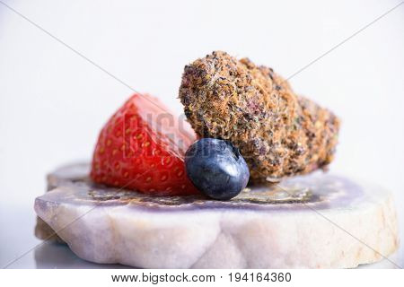 Detail of dried cannabis buds (Rockberry strain) with fresh fruit - medical marijuana concept background