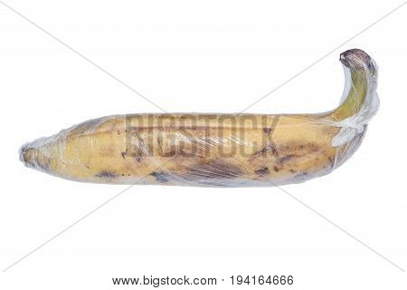 A ripe brown yellow banana is wrapped by preservative plastic film food protection concept.