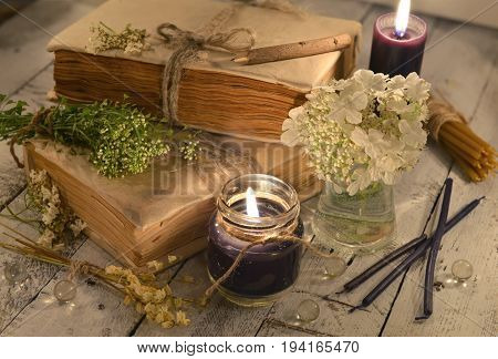 Old book with black candles and healing herbs and flowers. Alternative medicine, old pharmaceutic and homeopathic concept. Mystic and occult still life, vintage medical background