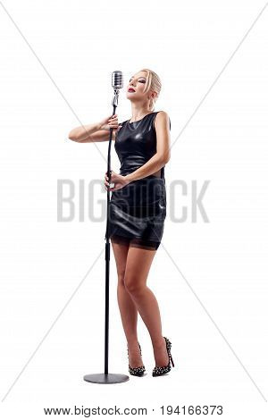Young blond woman in black leather dress holds a metal microphone in hands. Isolated white background.