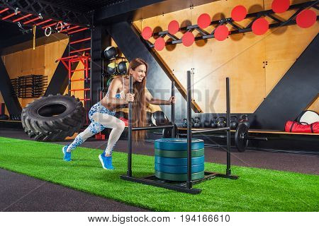 young slim woman working with heavy weights in the gym. Background: gym large car tires ladder horizontal bar rod vultures