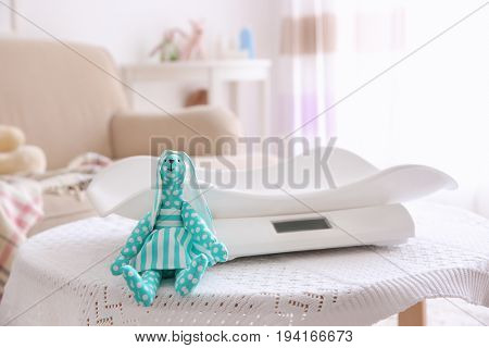 Toy near baby scales on table in light room