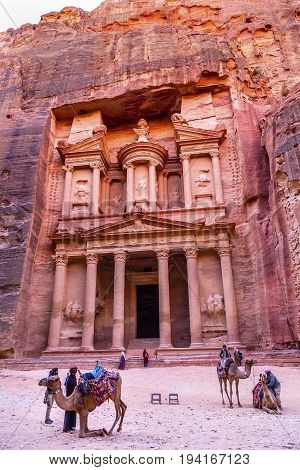 PETRA, JORDAN - NOVEMBER 26, 2017 Camel Heders Yellow Treasury in Morning Becomes Rose Red in Afternoon Camels Siq Petra Jordan Petra Jordan. Treasury built by the Nabataens in 100 BC. Canyon becomes rose red when sun goes. Inside buildings walls create m
