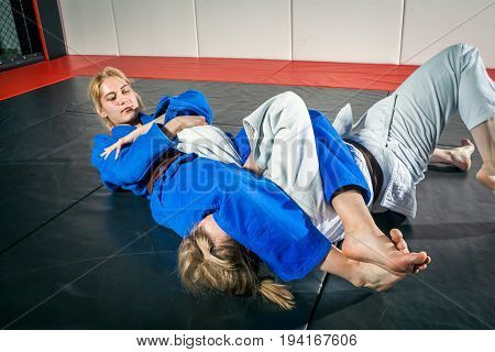 A young woman in a kimono makes a painful reception. Judo jujitsu. Tatami gym