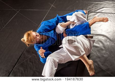 Judo Jiu Jitsu. Two women are fighting on tatami. Blue and white kimano. Painful reception. Ground floor