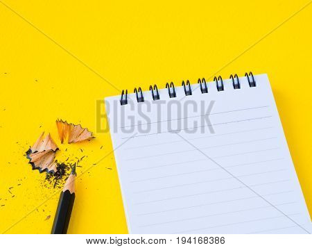 Sharpening a black pencil sharpener and the note book On yellow background. Education and business concept.