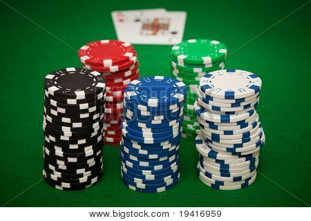 Gambling chips on green casino felt  and winning hand in blackjack