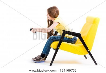 Lovely teen girl in yellow tshirt playing with joystick sitting in comfy yellow leather chair