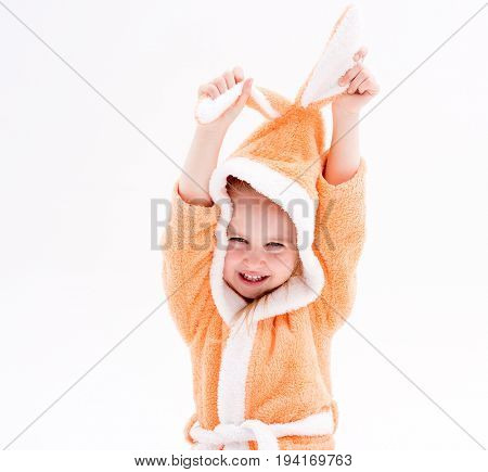 Active and playful little kid wearing peachy robes for bathing, playing with her bunny ears