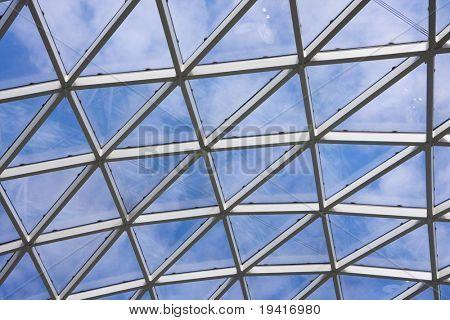Transparente Decke in moderne Bürogebäude. Blauer Himmel mit Wolken im Hintergrund.