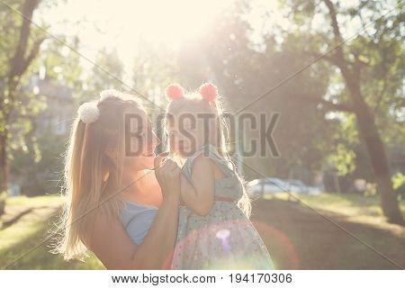Family values. Mother and daughter. Mother holding her baby in her arms. Same dresses and hairstyles. Backlight of the setting sun. Portrait in the park. Family look