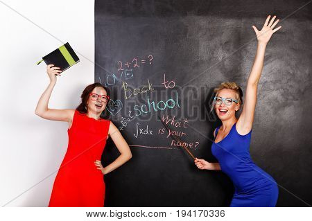 Two young attractive female students at school board. They are looking at board. One girl holds notebook another pointer. Back to school. Best friends forever. Welcome new students.