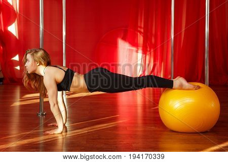 Pole dancer makes a stretch on the fitball before classes. Flexibility and plasticity. Young attractive sexy girl.