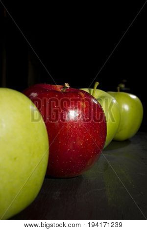 Red apple standing out in a row of green apples