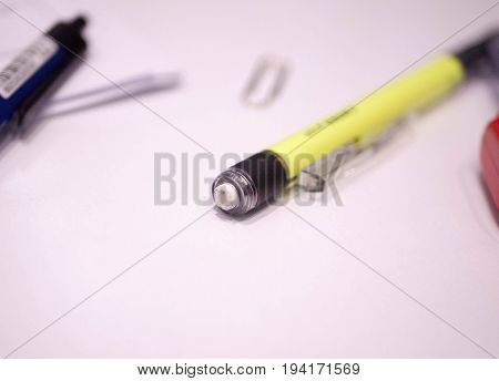 Pen, pencil, paper clip on the table.