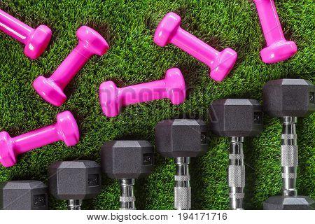 dumbbells on green artificial grass. texture, background