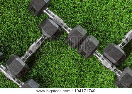 Metal dumbbells on green artificial grass. Pattern texture
