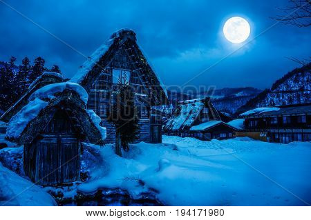 Snow covered the ground in winter season. Silhouette of town with night sky clouds and bright full moon on blue background serenity nature. High contrast. The moon taken with my own camera.