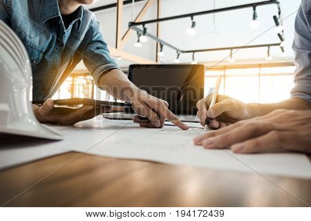 Two Architects Engineer Discussing  Data Working And Tablet, Laptop With Blueprint - Closeup On Hand