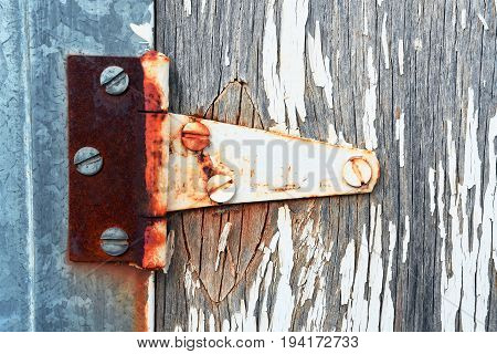An abstract image of an old rusted metal door hinge.