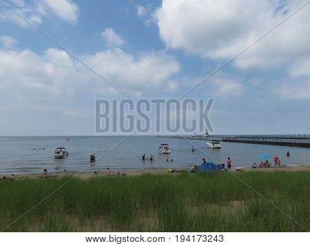 Silver Beach County Park in St. Joseph, Michigan with weather front lifting while beach goers enjoy their day.