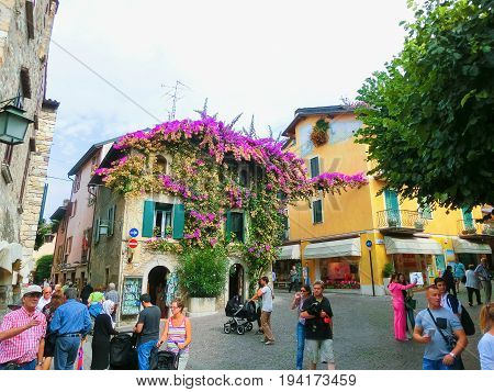 Sirmione, Italy - September 20, 2014: The people going at the Scaliger Castle at Sirmione, Italy on September 20, 2014. The famous castle of Sirmione and its small port are an uncommon example of a fortress used as a port. The building of this complex sta
