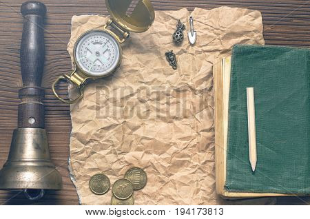Adventurer western reward page treasure hunt or travel concept. Compass money diary book train conductor bell pencil and blank crumpled brown page paper on wooden table.